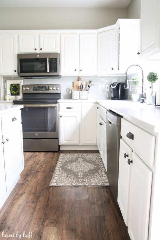White kitchen cabinets, a small rug by the sink, and stainless steel stove and microwave.