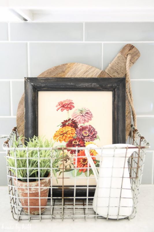 A small floral picture in a wire basket on the counter in the kitchen.