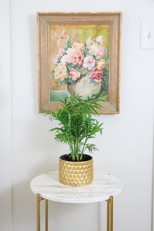 Vintage floral piece hanging just above a side table with a green plant on it.
