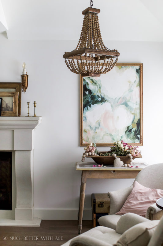 A pink, green and white floral picture in the living room beside a fireplace.