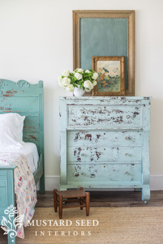 A distressed dresser in the bedroom with a small flower inspired art piece on top.
