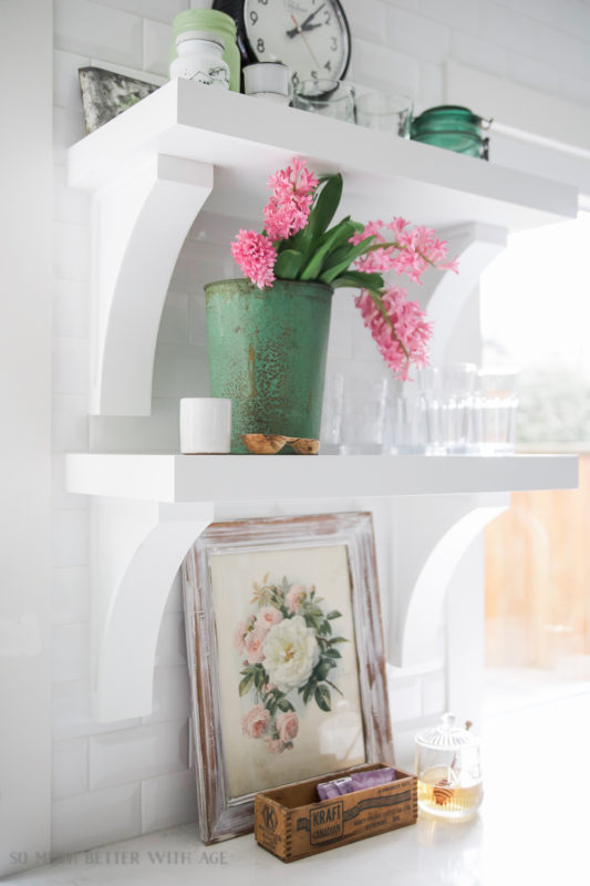 Open shelving in a white kitchen with a vintage looking floral picture on the counter.
