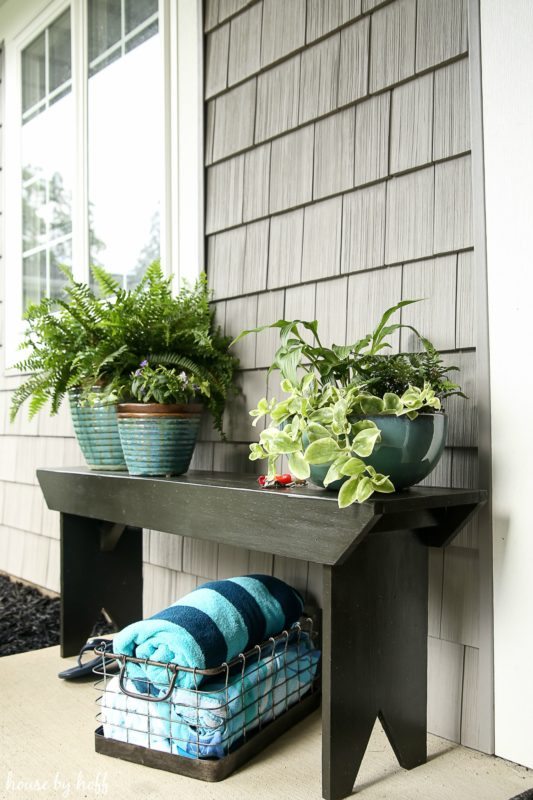 A five board bench with plants on it and towels underneath in a wire basket.