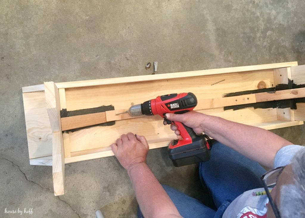 Using an electric screw driver on the bench.