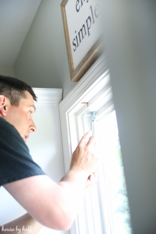 A man installing the blinds in the kitchen.