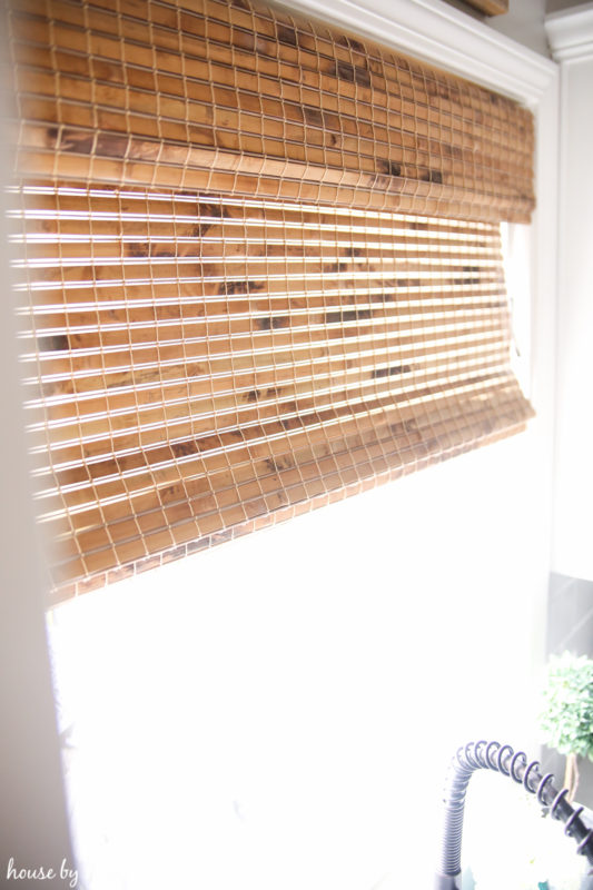 The woven blinds in the kitchen behind the sink.