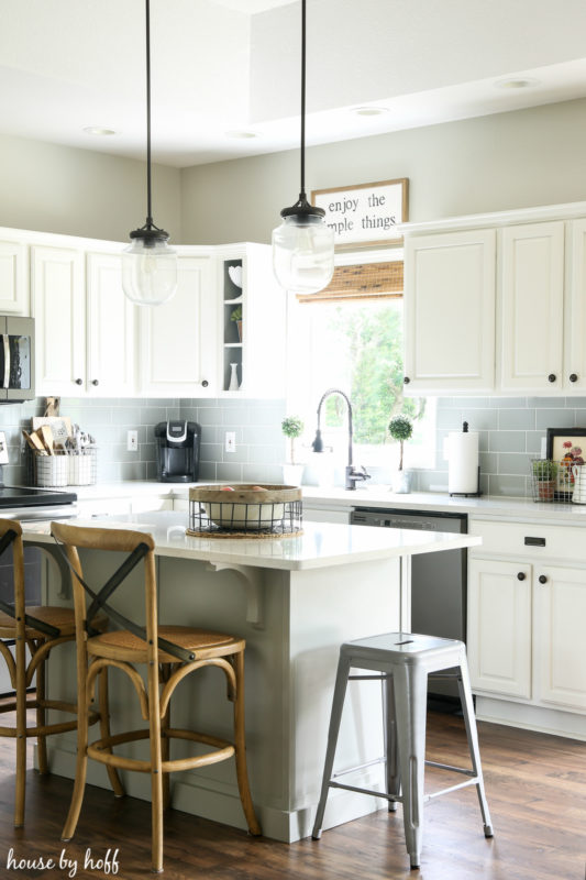 The white kitchen island with wooden chairs.