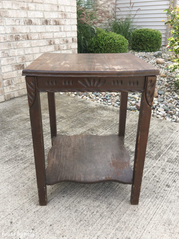 An old brown worn out side table outside in driveway.