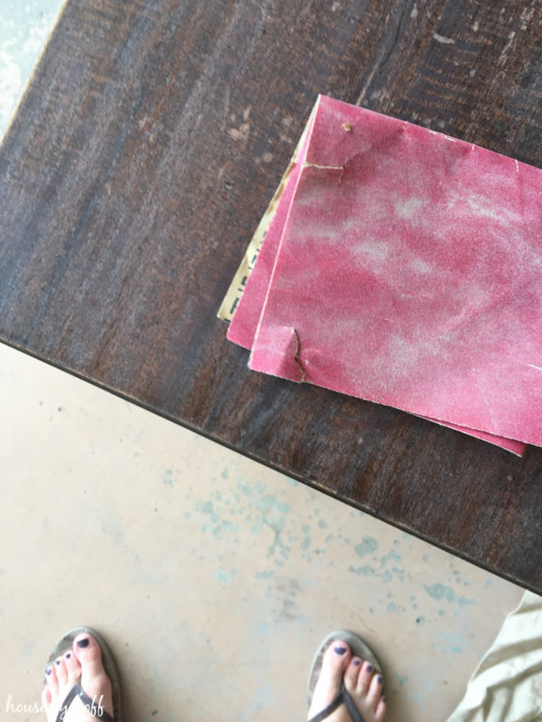 Sanding the brown worn out table.