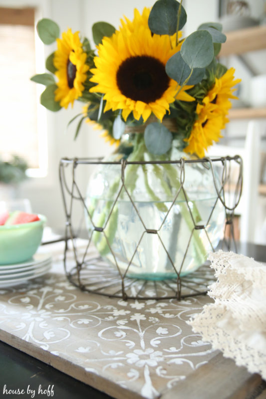 Large yellow sunflowers in vase in a metal wire basket on the tray.