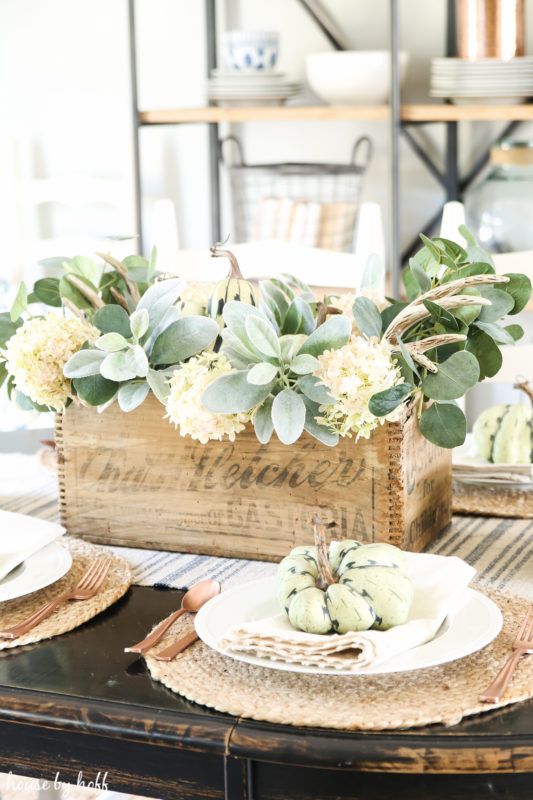 Dining table with a Woden box centrepiece filled with eucalyptus and hydrangeas.