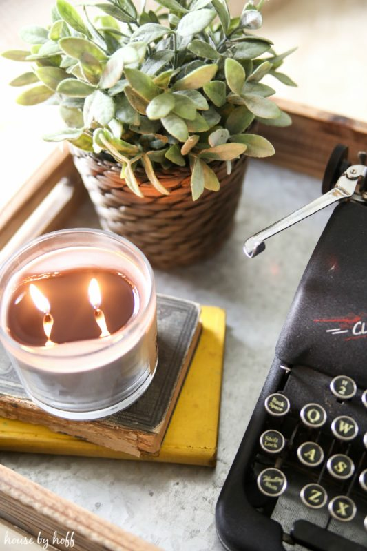 Lit candle and green plant beside typewriter.