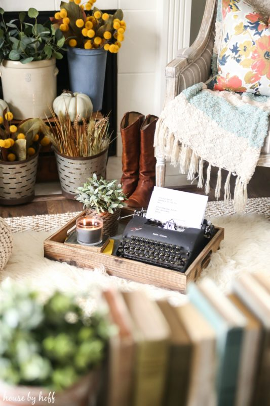Typewriter on floor in front of fireplace.