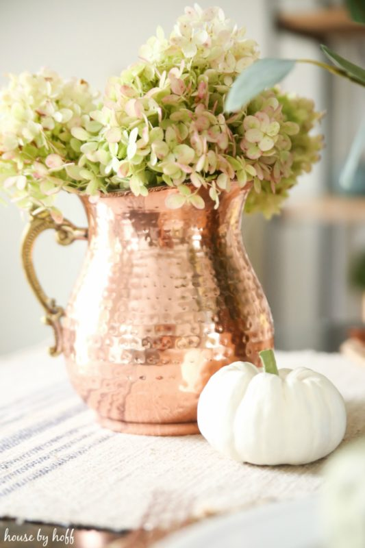 Large copper pitcher with hydrangeas in it and a small white pumpkin beside it.