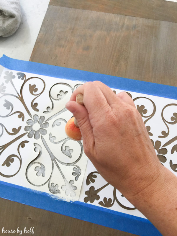 Stenciling onto the piece of wood.