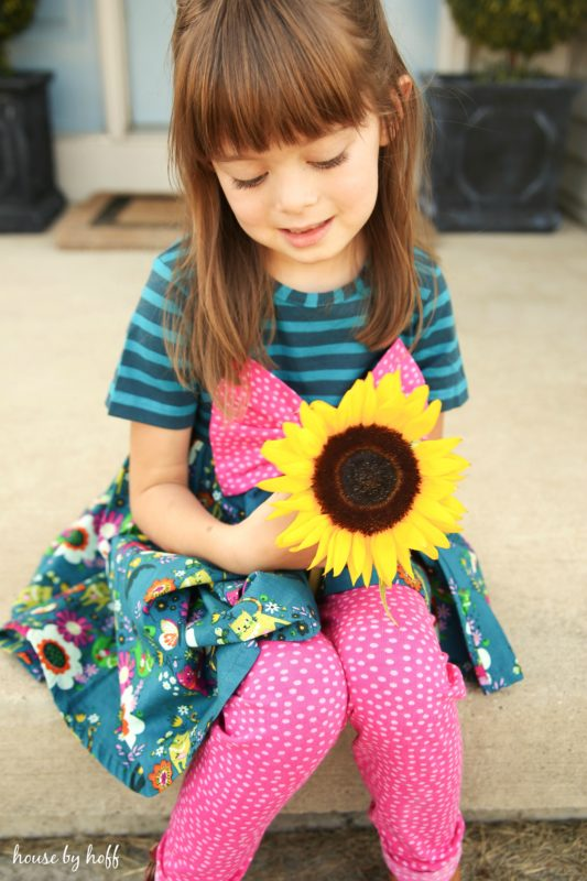 Little girl with a sunflower in her hand wearing pink pants and pink bow.