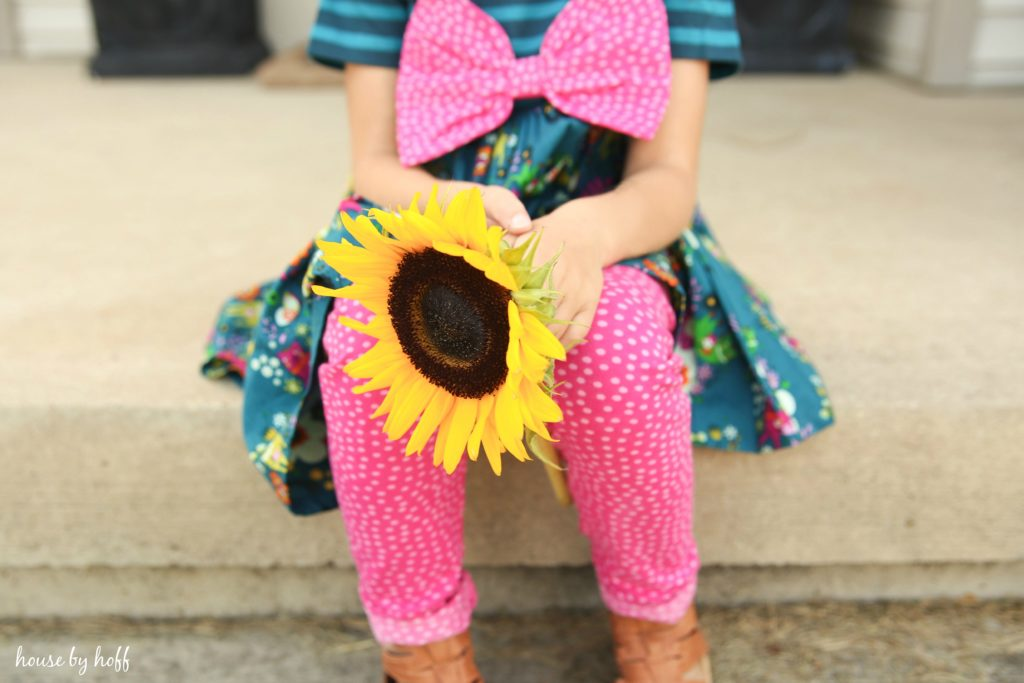 The girl sitting on the front porch steps with a large yellow sunflower in her hand.