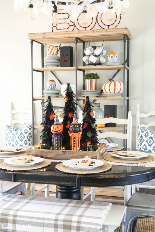 Decorated Halloween table with open shelving unit behind it decorated with pumpkins.