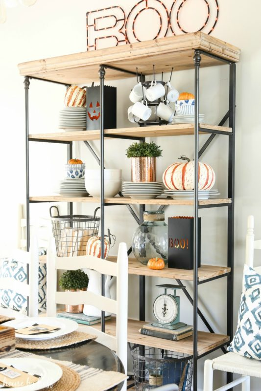 Open shelving unit with Boo sign on top of it, lit up.