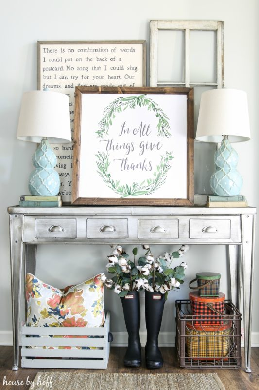 Pewter side table with framed printable on top and two light blue lamps.