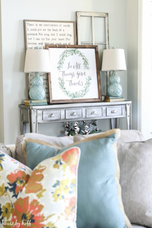 Side table with the November vignette on it and pillows in the foreground.