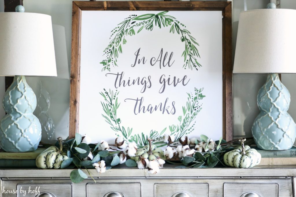 Framed In All Things Give Thanks poster on the pewter side table.