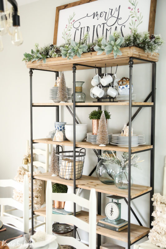 Shelving unit with garland and trees on it.