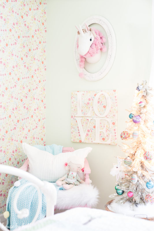 A small unicorn is on the wall with a decoration around it.