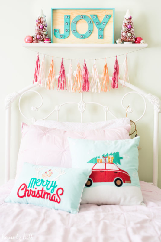 Merry Christmas pillows are on the bed and a JOY sign.