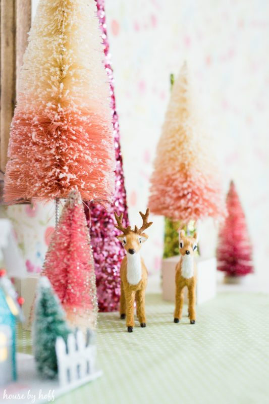 Up close picture of the little reindeer figurines beside the trees.