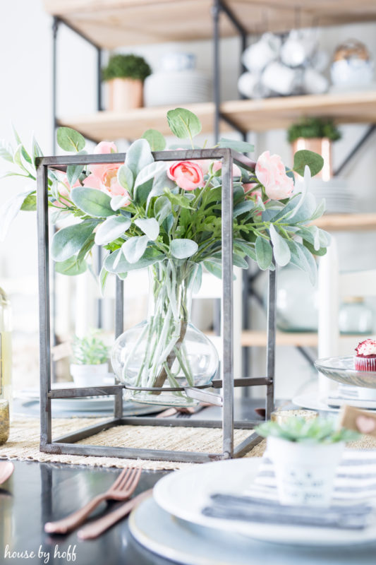 Soft pink roses in a rustic metal box holding the clear vase on the table.
