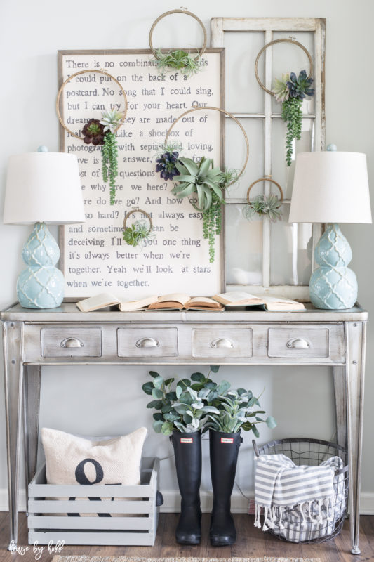 Faux green plant wreaths hanging on wall above table.