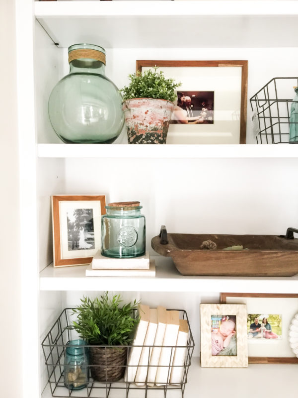 Open white shelves with picture, glass vase and wire baskets.