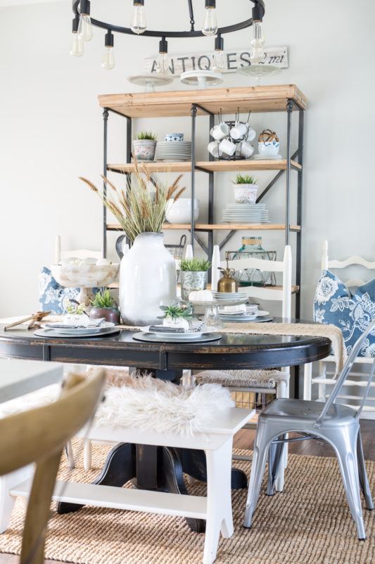 Wooden dining table with white vase filled with wheat and neutral decor.