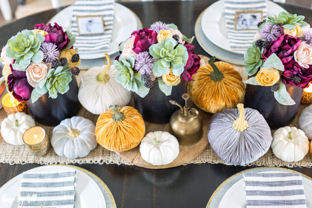 Fall table setting with velvet pumpkins, floral arrangements in a black vase and white plates on table.