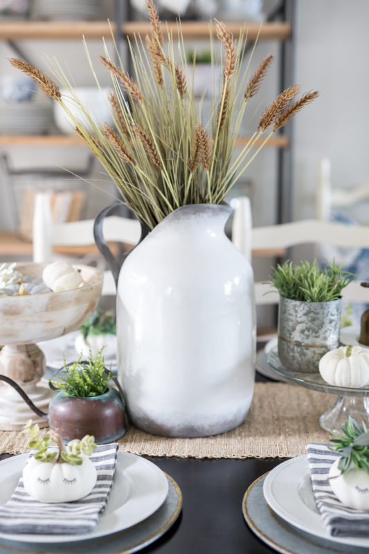 White vase filled with wheat on the table.