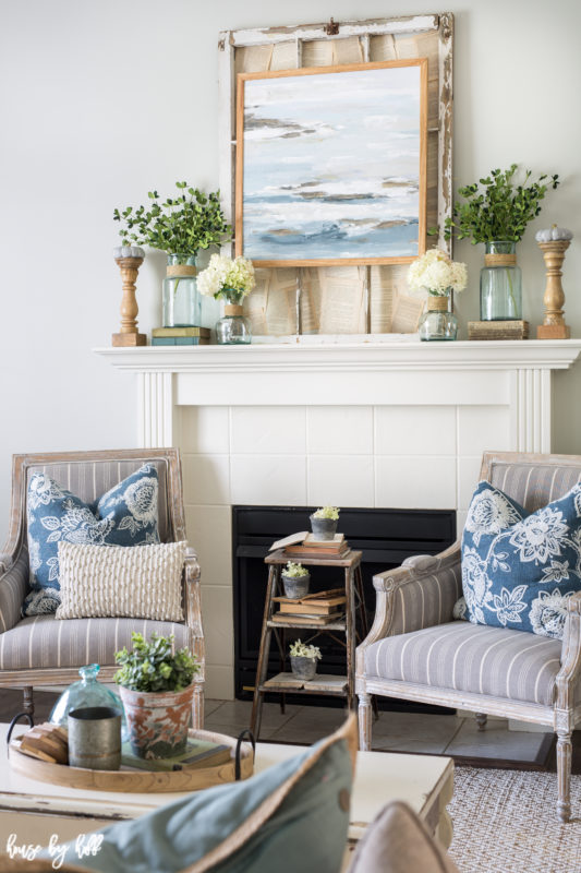 White mantel with armchairs in front of it and a side table.