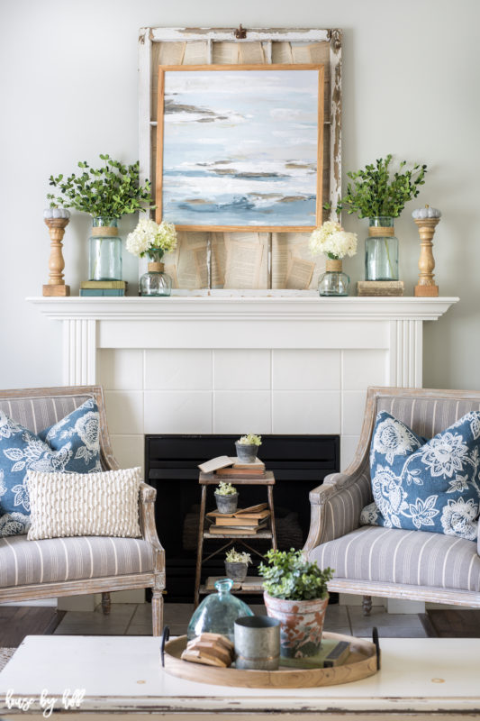 White fireplace with a ocean picture above it and 2 armchairs beside the fireplace.