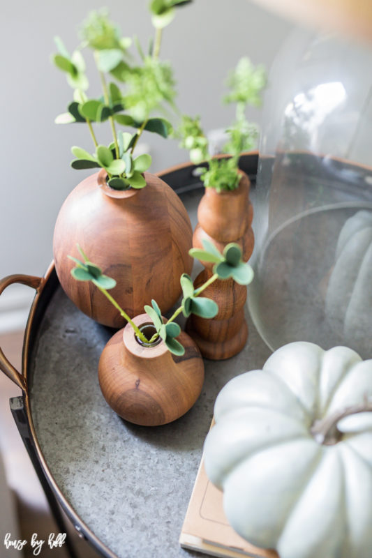 Wooden little vases with green plants in them on a serving tray.
