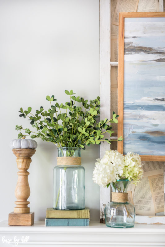 Vases with flowers and leaves and a candelabra on the mantel.
