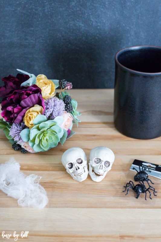 Skull heads, flowers, mesh and a black vase on the counter.