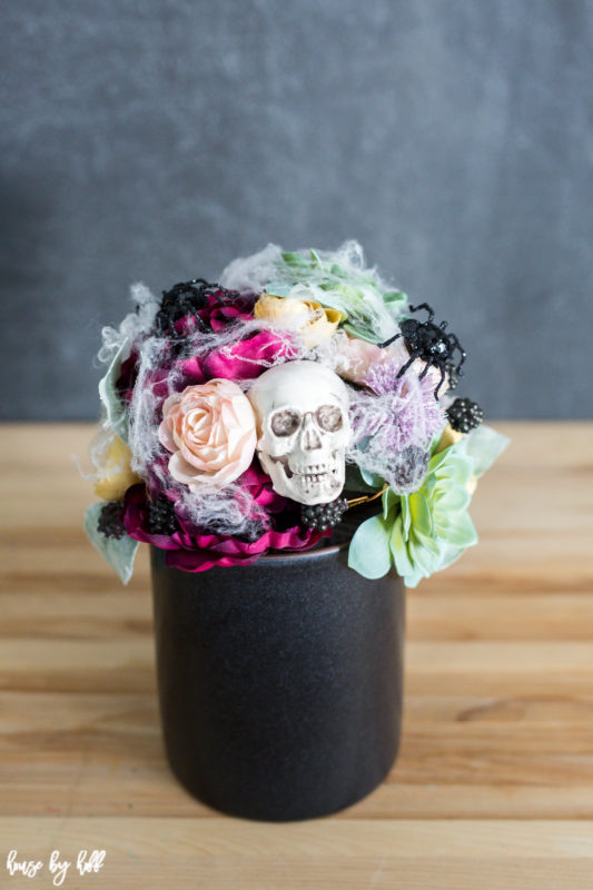 Succulents and flowers with spider web around them and skulls all in a black vase on a table.