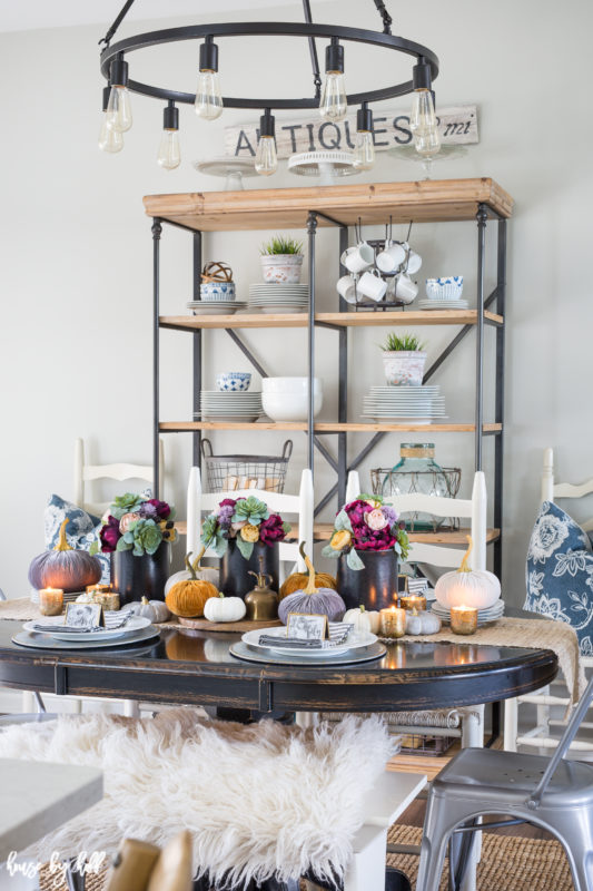 Decorated dining table for fall with shelving unit in the background.