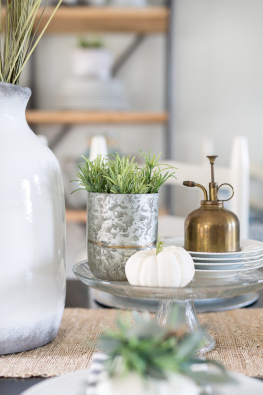 Brushed brass olive oil canister on a white plate with succulents in a silver container on the table.