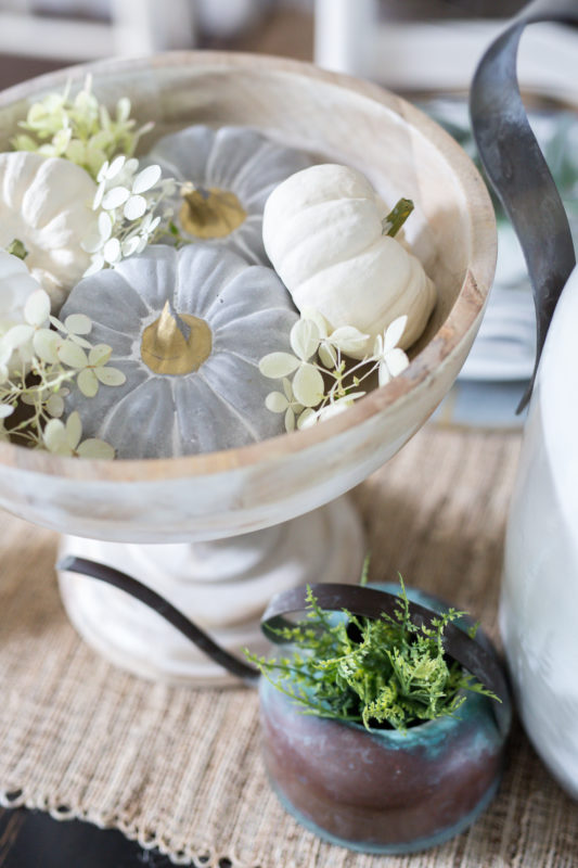 Pedestal bowl filled with neutral little pumpkins on the table.