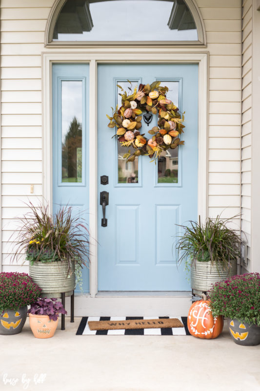Blue front door of a house with a Fall wreath on it.