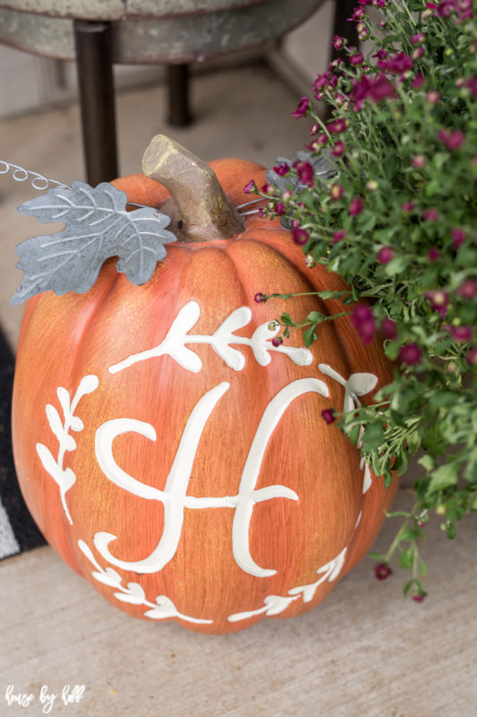 Monogramed orange pumpkin with purple flowers beside it.