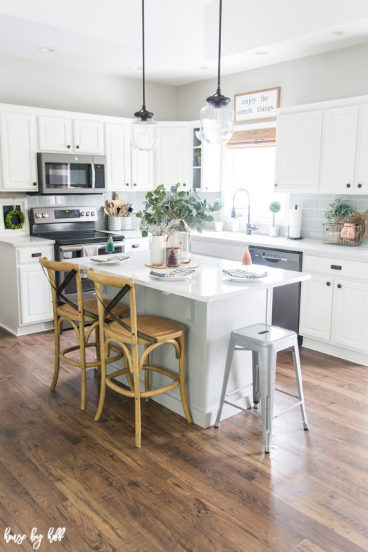 A mostly white kitchen with an island and two chairs.