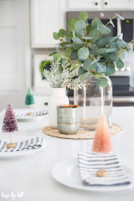 Eucalyptus leaves in a clear glass jar is in the middle of the kitchen island.