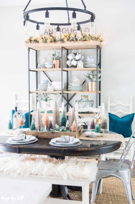 A colorful holiday dining room with teal pillows, faux white fur on the bench and multi colored mini Christmas trees as a centerpiece.